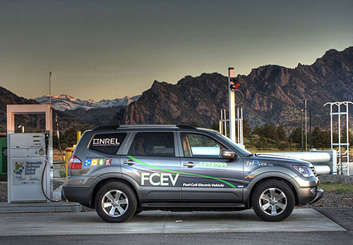 SUV vehicle in front of a fueling station with mountains in the background.